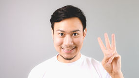 A man showing hand sign the third thing. An asian man with white t-shirt and grey background stock image