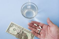 Man showing hand with white pills above light pastel blue background desk with money, coins and a glass of fresh water. Healthcare, medical concept in Flat Lay stock photos