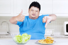 Man showing healthy and unhealthy food 1. Man showing healthy and unhealthy food in the kitchen Stock Images