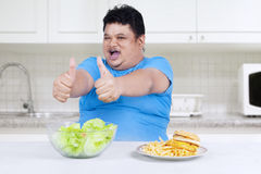 Man showing healthy and unhealthy food 2. Man showing healthy and unhealthy food in the kitchen Royalty Free Stock Photography