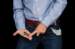 Man showing his empty pocket. And holding coin in hand on black isolated background. The guy shows your last money. The guy counts the money. Poor student Royalty Free Stock Images