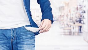 Man showing his empty pocket. On blurred shopping mall background Stock Image