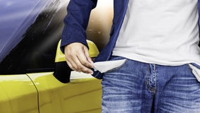 Man showing his empty pockets with yellow car background. Stock Photography