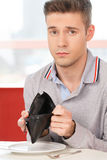 Man showing his empty wallet in cafe. Royalty Free Stock Photo