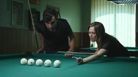Man Showing His Girl Where To Hit The Ball - Young Woman Receiving Advice On Shooting Pool Ball While Playing Billiards.  stock footage