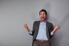 Man showing his happiness and success. Portrait of positive casual young man wearing tweed jacket and red bow tie. Man showing his happiness and success Royalty Free Stock Image