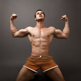 Man showing his muscles like a winner Royalty Free Stock Photography