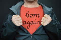 Man with words born again on his red t-shirt. A man showing his t-shirt with the words born again written on it stock photos