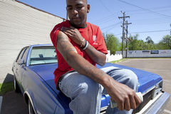 Man showing his tattoos, Mississippi. A man sat on the hood of his car showing the camera the tattoos on his arm, Mississippi stock image