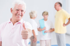 Man showing his thumb up. Elderly men showing his thumb up at the gym Royalty Free Stock Photo