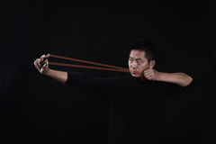 A man showing how to stretch rubber band of slingshot Royalty Free Stock Image