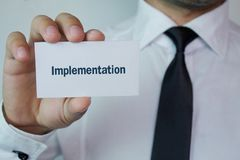 Man showing Implementation word on business card. Business concept Royalty Free Stock Image