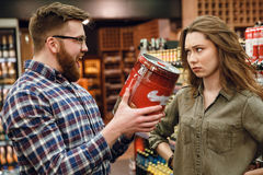 Man showing keg of beer to your woman. Happy Man showing keg of beer to your displeased women while being in supermarket Stock Image
