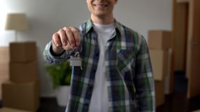 Man showing key from apartment, affordable lending, investment in real estate. Stock photo royalty free stock image