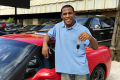 Man showing key of new red sports car. Happy man showing key of new red sports car Royalty Free Stock Photography