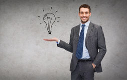 Man showing light bulb on the palm of his hand. Business, office, advertising and people concept - friendly young buisnessman showing light bulb on the palm of Stock Images