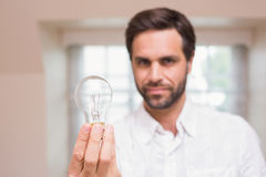 Man showing light bulb to camera Royalty Free Stock Photography