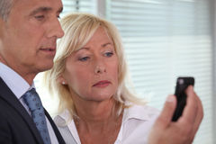 Man showing mobile phone to woman Stock Photos