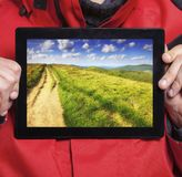 Man showing mountains on tablet. Travel Royalty Free Stock Image