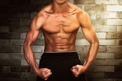 Man showing muscle. On brick wall background Royalty Free Stock Photography