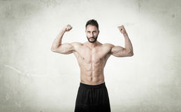 Man showing muscles in abstract room. Textured wall Stock Photography