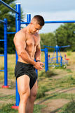 Man showing muscles in street workout park. Man showing muscles in a street workout park Stock Images