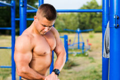 Man showing muscles in street workout park. Man showing muscles in a street workout park Royalty Free Stock Photos