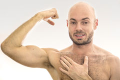 Man showing off his muscles. On a white background Royalty Free Stock Image