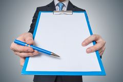 Man is showing and offering blank white paper in clipboard with pen Stock Image