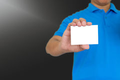 Man showing pasteboard. Man in blue t-shirt showing pasteboard with right hand on gray background Royalty Free Stock Photo