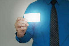 Man showing pasteboard. Closeup light at card in right hand of blue shirt man on gray background Royalty Free Stock Image