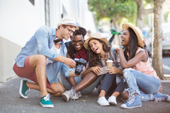 Man showing photos in camera to his friends Royalty Free Stock Photos