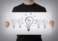 Man showing picture with light bulbs Royalty Free Stock Photography