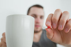 Man showing a pill and and a mug Stock Photography