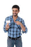 Man showing and pointing blank business card smiling happy. Young attractive man in casual shirt and jeans showing and pointing blank business card smiling happy Stock Photos