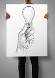 Man showing poster of Hand drawn light bulb Stock Photo