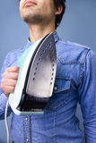 Man showing pride in domestic chores. Young multiracial man posing with an iron in a proud pose Stock Photos