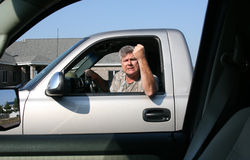 Man showing road rage. Man with fist in the air showing symptoms of road rage Royalty Free Stock Images
