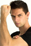 Man showing he's arm muscles. And looking seriously Stock Image