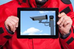Man showing security system camera on tablet Stock Photos