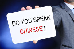 Man showing a signboard with the question do you speak chinese? Royalty Free Stock Images