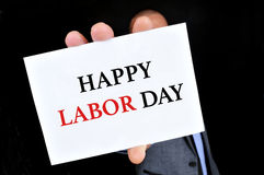 Man showing a signboard with the text happy labor day Royalty Free Stock Photos