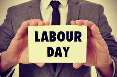 Man showing a signboard with the text labour day, filtered. A young caucasian man wearing a gray suit shows a signboard with the text labour day written in it Royalty Free Stock Images