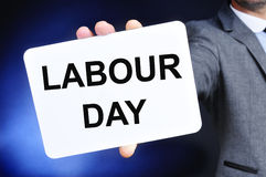 Man showing a signboard with the text labour day Stock Images