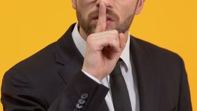 Man showing silence sign, warning about threat, non-disclosure agreement. Stock footage stock footage