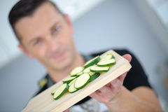 Man showing sliced cucumber laying on wooden chopping board. Man showing sliced cucumber laying on a wooden chopping board Royalty Free Stock Photos