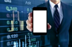 Man showing smartphone with stock chart background Stock Photo