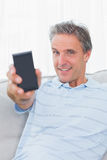 Man showing smartphone to camera and smiling Stock Image
