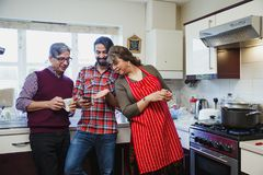 Man Showing Smartphone to Parents. Mid adult men is showing his parents something on his smartphone while they are in the kitchen of their home Royalty Free Stock Photography