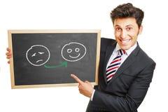 Man showing smileys on blackboard Stock Images